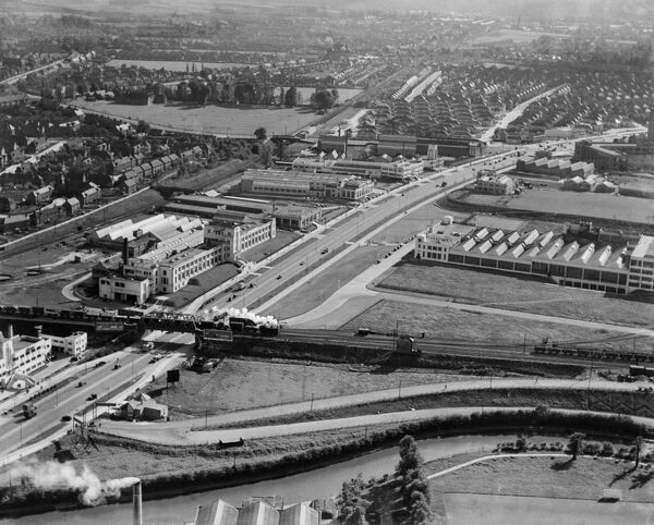 Great West Road, Brentford, Middlesex. A steam train crosses a railway bridge over the Great West Way. The Pyrene Building (centre left), built 1928 by Wallis, Gilbert and Partners, is Grade II listed. Aerial view by Aeropictorial. Aerofilms Collection