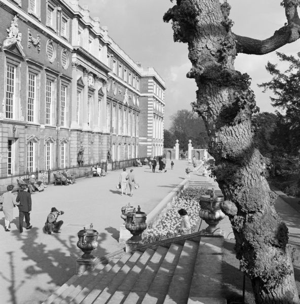 HAMPTON COURT PALACE, Greater London. People strolling outside the south front to Hampton Court Palace with a man crouched taking a photograph of a woman, a pollarded tree in the foreground. Photographed by John Gay. Date range: 1955-1965
