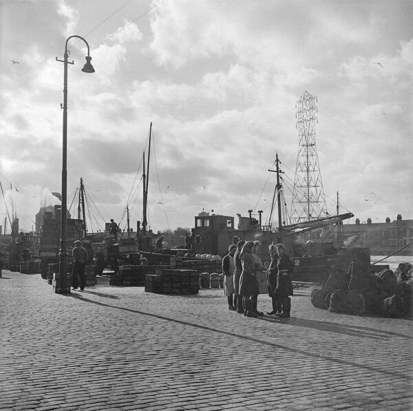 Great Yarmouth, Norfolk. A group of women, possibly Scottish herring girls, on the quay with herring boats beyond