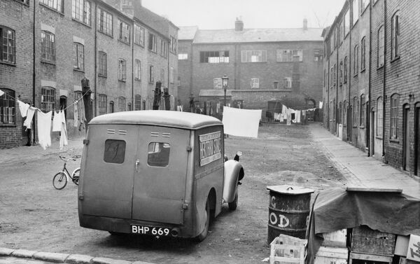 "Hertford Square, Coventry, West Midlands, 1953. John M Prest (1908-€""86), silver gelatin DOP (developing out paper) print. A van and lines of washing form a significant part of John Prest'€™s view of weavers'€™ housing in Hertford Square"