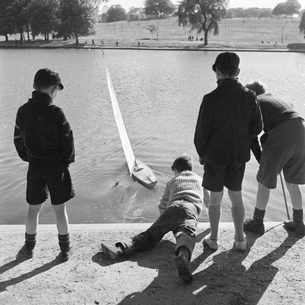 HIGHGATE PONDS, Hampstead Heath, Greater London. Three boys standing watching a model yacht being launched on one of the Highgate Ponds by a boy lying on his front reaching over the water. John Gay. Date range: 1960-1965