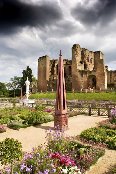 KENILWORTH CASTLE, Warwickshire. The north facade of the great tower viewed from across the Elizabethan garden. Bedding plants, obelisks and marble fountain under a stormy sky
