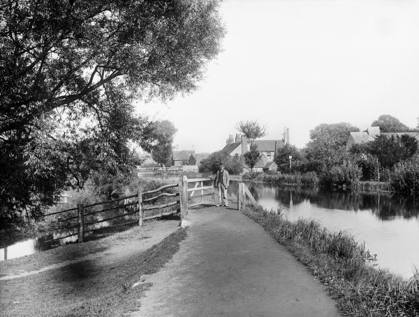 GREENHAM, Newbury, Berkshire. Looking east from beyond the wharf along the Kennet towpath, with a man passing through the gate ahead. Photographed in 1890 by Henry Taunt
