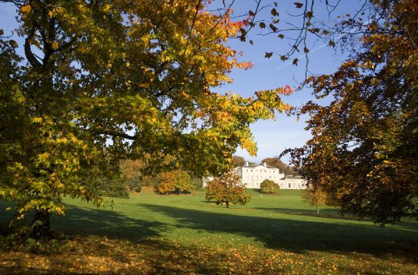 KENWOOD HOUSE, London. Distant, south front, exterior view of the house through parkland trees, with autumn leaf colour
