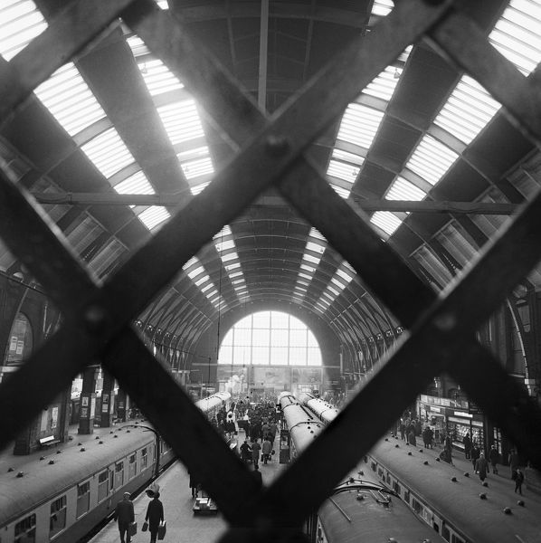 KINGS CROSS STATION, London. Interior view looking down through the trellis of the elevated footbridge, onto the passengers, trains and platforms beneath. Photographed by John Gay. Date range: 1960-1972