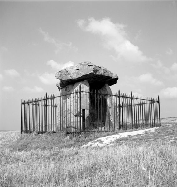 KITS COTY, near Maidstone, Kent. The exterior of the megalithic monument surrounded by modern, protective railings. It was originally covered by a long barrow that measured 200 feet long. Photographed by Stanley W Rawlings. Date range: 1945 - 1965