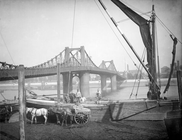 LAMBETH SUSPENSION BRIDGE, London. The bridge was constructed across the River Thames in 1861-2. In the foreground a crane unloads bricks from a barge onto a horse drawn cart. Photographed late 19th century by Henry Taunt