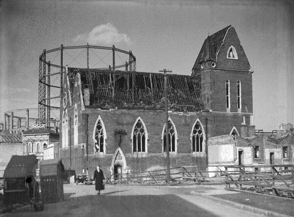 St John's Church, Halley Street, Limehouse, London. The church from the south showing its damaged roof, with gasometers beyond. The church has since been demolished. Photographed By Herbert Felton 1940-1944. The negative is in poor condition