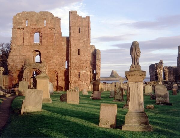 LINDISFARNE PRIORY, Holy Island, Northumberland. A view of the priory in the late afternoon with Lindisfarne Castle in the distance