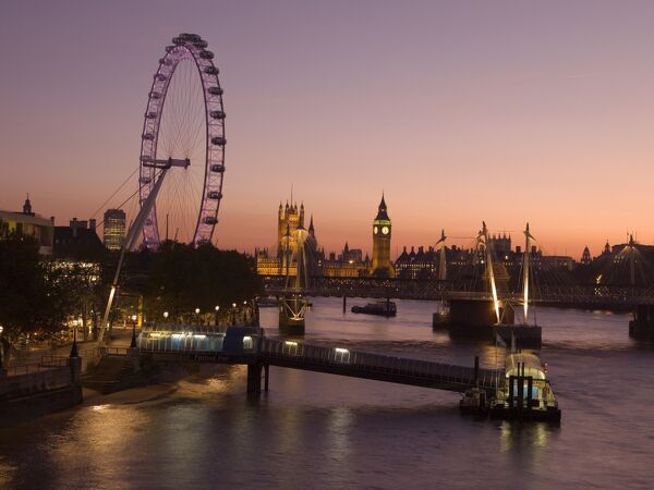 Late evening view from Waterloo Bridge along the River Thames towards the London Eye and the Palace of Westminster including Big Ben clock tower