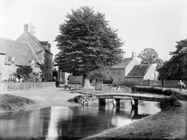 LOWER SLAUGHTER, Gloucestershire. Looking through the village with a small rustic footbridge crossing the River Eye. Photographed in 1890 by Henry Taunt