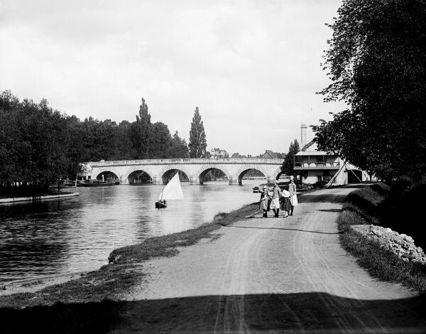 MAIDENHEAD BRIDGE, Maidenhead, Berkshire. The north aspect of the bridge seen from the Buckinghamshire bank, with a small party of girls walking along the riverside path. The graceful bridge is built from Portland stone and was constructed in the 1770s