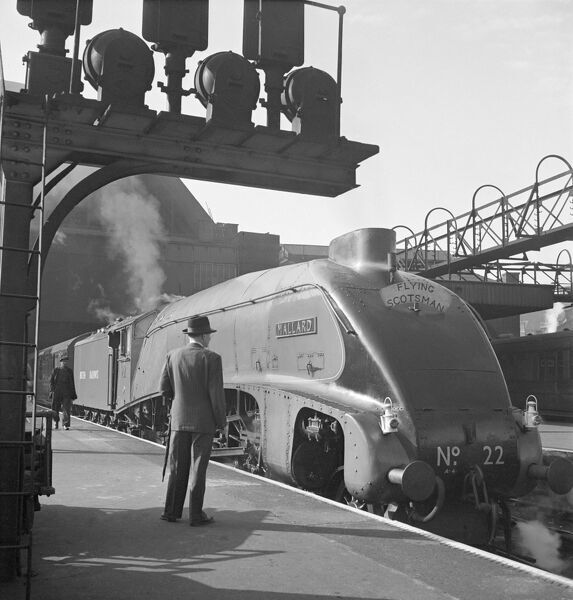 MALLARD. View of the LNER Class A4 train during its time on the Flying Scotsman express passenger service between London and Edinburgh. A man in a trilby hat looks at the engine. Photographed by John Gay, 1948