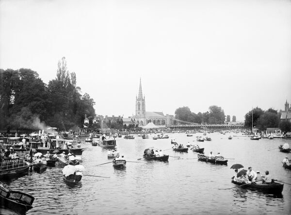 MARLOW, Wycombe, Buckinghamshire. A view of the river filled with small row boats and houseboats during the regatta held annually between at least 1855 and 2001 on the River Thames (it has since transferred to Dorney Lake). With All Saints Church