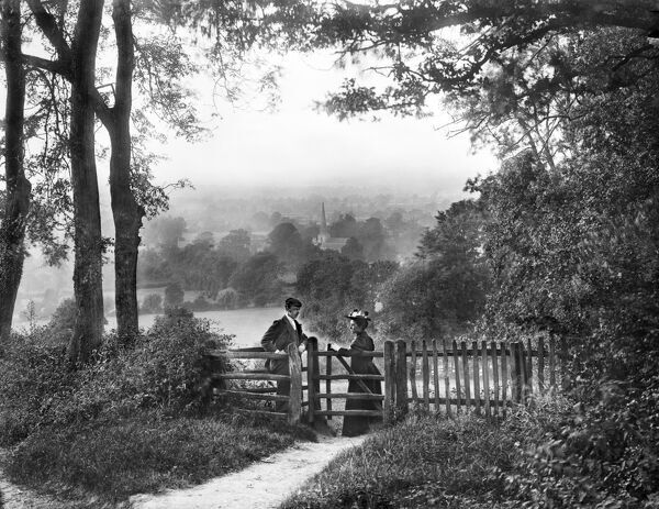 MICKLETON, Gloucestershire. A couple posing by a gate with the spire of St Lawrence's Church and surrounding countryside in the background. Photographed by Henry Taunt (active 1860-1922)