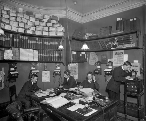 An interior view of a crowded office. D M Gant was a turf accountant based at 25 Conduit Street, London. Photographed by Adolphe Augustus Boucher, a photographer for Bedford Lemere & Co, 1 April 1909