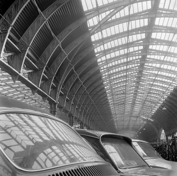 PADDINGTON STATION, London. Interior view showing the roof of Paddington railway station reflected in the windows of parked cars. John Gay. Date range: 1960-1972