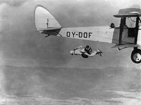 Parachutist descending 1930s. Jumping off the trailing edge of the lower wing of a biplane. Aerofilms Collection (see Links)
