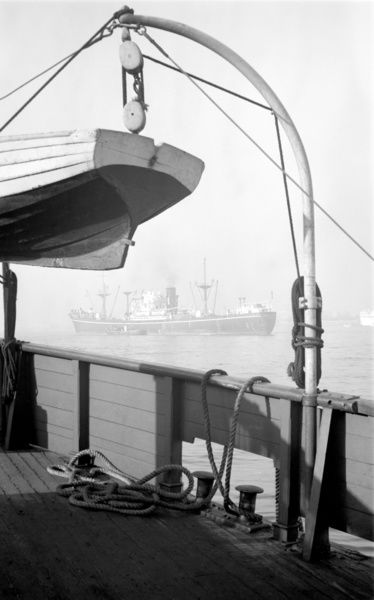 View of passing ship, Gravesend Reach, Kent. A distant view of shipping in Gravesend Reach as seen from the deck of another boat with the stern of a raised lifeboat in the foreground. Photographed by Stanley W Rawlings. Date range: 1945 - 1965