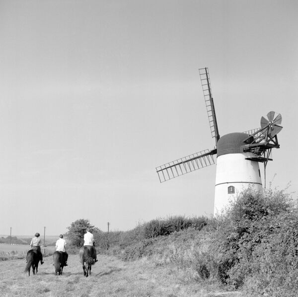 PATCHAM, East Sussex. Three horsemen ride past Patcham tower mill on the Downs behind Brighton. Photographed by Eric de Mare (active 1945-80)