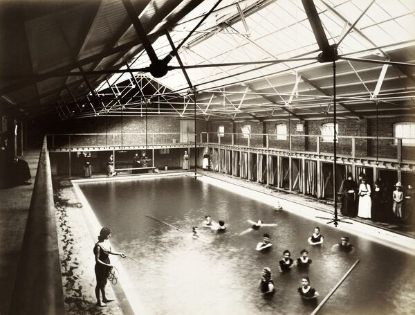 PEOPLES PALACE, Mile End Road, Stepney, London. Interior view looking down from the balcony towards the swimming pool during a female swimming session. Photographed by Bedford Lemere, 12th June 1888