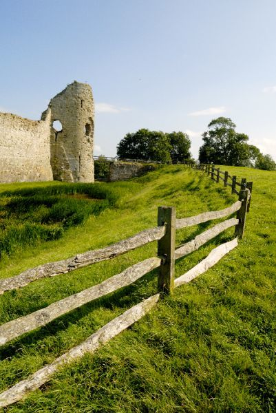 PEVENSEY CASTLE, East Sussex. The gatehouse and moat viewed from the north west with fence in the forground