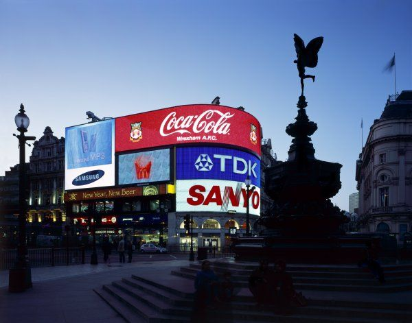 PICCADILLY CIRCUS, City of Westminster, London. General view at dusk showing neon signs and silhouette of the Shaftesbury Memorial, ' Eros ' The Angel of Christian Charity