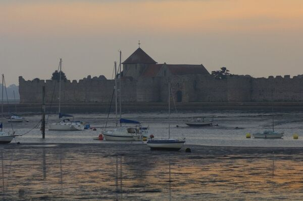 PORTCHESTER CASTLE, Hampshire. Viewed from across the estuary at dusk