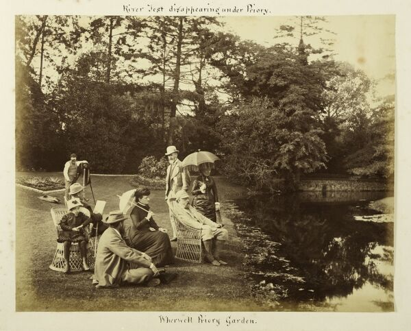 Group portrait in the grounds of The Priory, Wherwell, Hampshire. Members of the Iremonger family, owners of The Priory from the mid-18th century until 1914, are probably among those trying to look relaxed beside the River Test. Another photographer