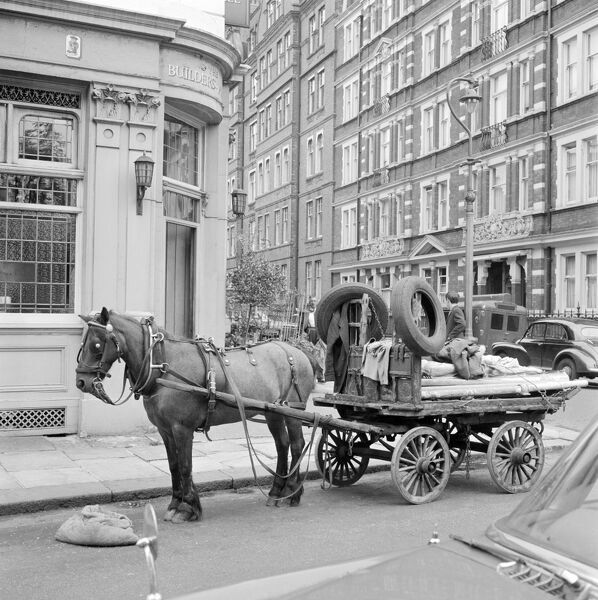 A horse-drawn rag and bone cart standing on the road outside the Builders Arms public house at 1 Kensington Court Place, Kensington, London, with St. Albans Mansions visible beyond. John Gay. Date range: Jan 1962 - May 1964