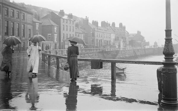Pier Road, Whitby, North Yorkshire. People with raincoats and umbrellas walking beside the harbour in the rain. Photographed by Alfred Newton and Sons 1896-1920