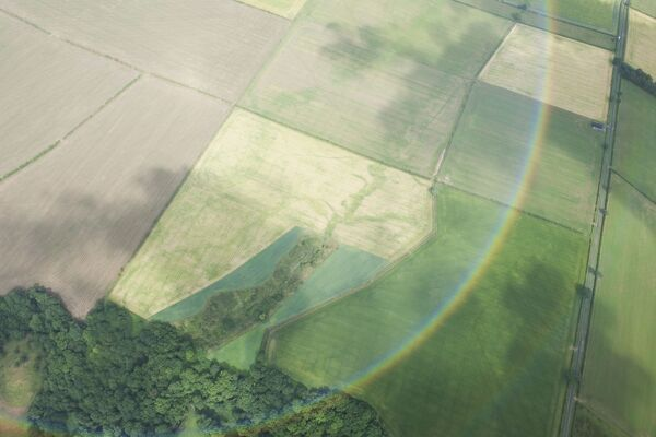Nether Welton, Cumbria. Aerial view showing crop mark evidence of a paleochannel (the former path of an extinct watercourse) viewed through a rainbow. NY3446/9