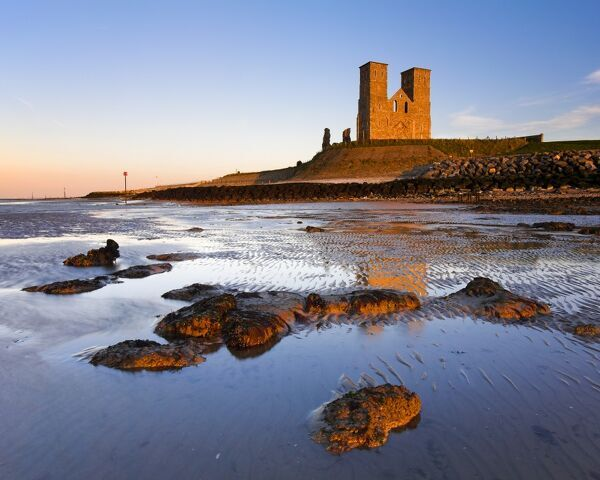 RECULVER TOWERS AND ROMAN FORT, Kent. Twin 12th-century church towers bathed in the warm glow of the setting sun at low tide