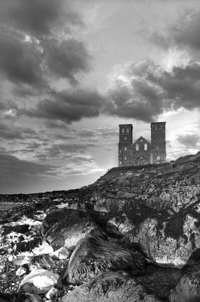 RECULVER TOWERS AND ROMAN FORT, Kent. Twin 12th-century church towers in late afternoon sunshine with scattered clouds - monochrome