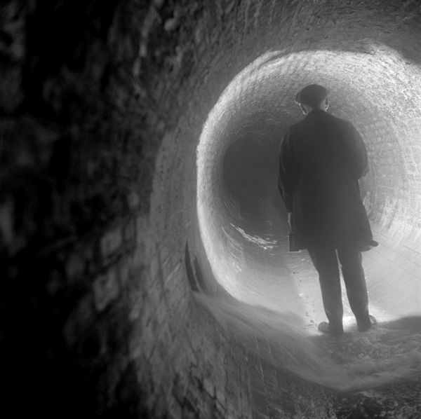 REGENT STREET SEWER, Regent Street, Westminster, Greater London. A workman looking along the Regent Street sewer by torchlight. Photographed by Eric de Mare. Date range: 1945-1980