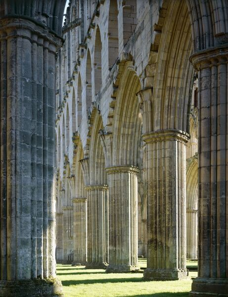 RIEVAULX ABBEY, North Yorkshire. The arches on the south side of the presbytery from the east end of the abbey church - autumn sunshine