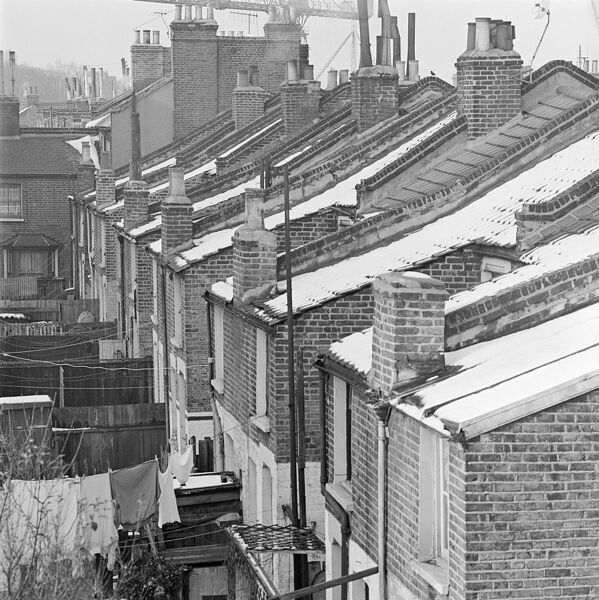 A view from roof level along the snowy roofs of a line of terraced brick houses, showing chimneys, the back gardens of the houses, and with a large crane visible in the distance above the roofs. Possibly located near London Docks. Photographed by John Gay