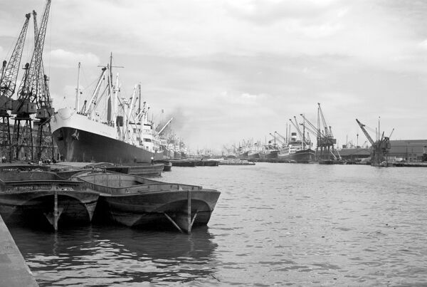 ROYAL DOCKS, Silvertown, Canning Town, London. Shipping moored by the dockside including barges in the foreground. Photographed by Stanley W Rawlings. Date range: 1945 - 1965
