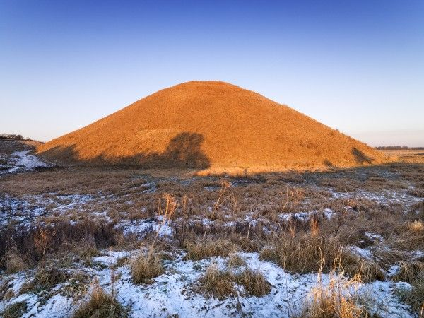 SILBURY HILL, Avebury, Wiltshire. Early morning light illuminates Silbury Hill showing the remains of a hard frost in the foreground