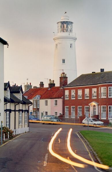 SOUTHWOLD, Suffolk. Traffic passes the lighthouse at dusk