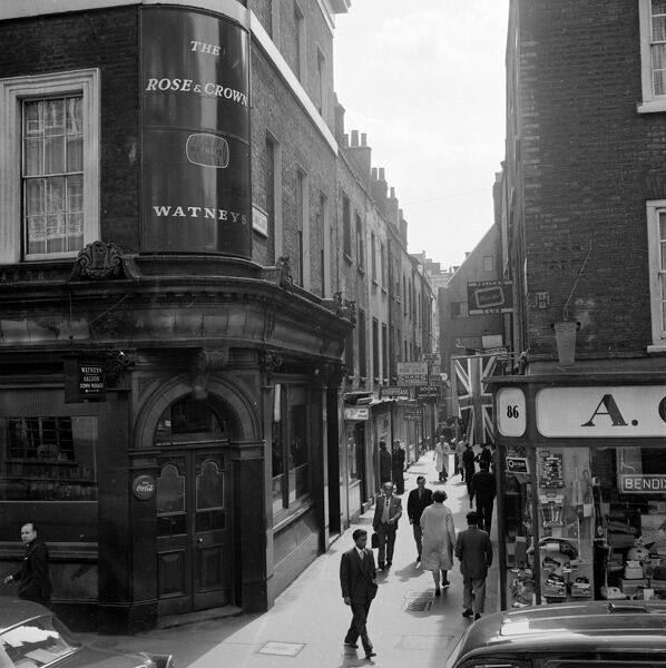 St Anne's Court, Soho, City of Westminster, Greater London. View along St Anne's Court, Soho, showing signs for clubs and shops, with the corner of the Rose & Crown, Dean Street, in the foreground. Photographed by John Gay in the early 1960s