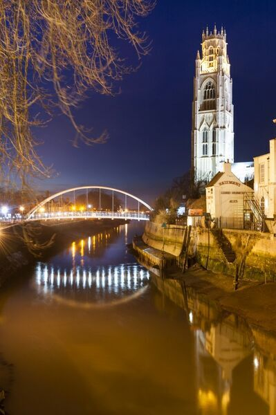 St Botolph's Bridge, Boston, Lincolnshire. The new footbridge over the river Haven from the south, illuminated at dusk, with St Botolph's church beyond