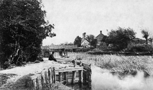 ST JOHN'S LOCK, Lechlade, Gloucestershire. The weir and lock keeper's house at St John's Lock on the River Thames. A man sits on the riverbank and contemplates the reeds. (Published in Taunt's 'New Map of the River Thames&#39