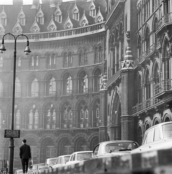 ST PANCRAS CHAMBERS, London. The south facade of the station with a man walking along the pavement beside a row of parked cars. Date range 1960-1972. John Gay