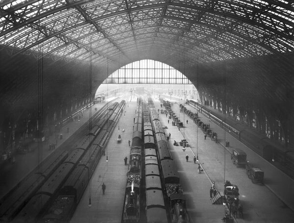 ST PANCRAS STATION, Camden, London. An interior view of St Pancras Station, looking down on the platforms which are busy with commuters. A line of hackney cabs wait for fares to the right of the photograph. The station was designed by W. H. Barlow in 1868