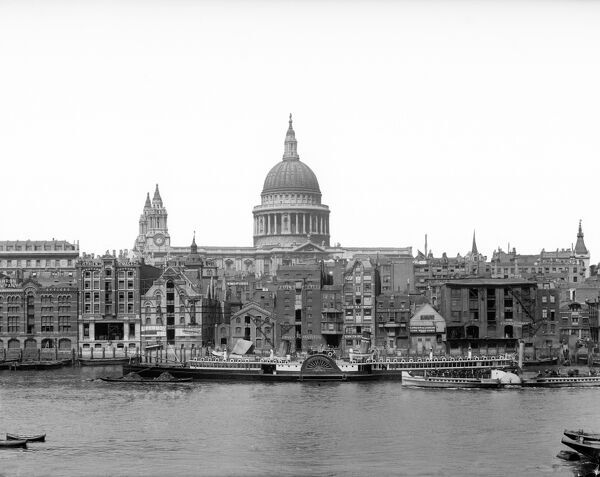 ST PAUL'S CATHEDRAL, City of London. A general view looking across the River Thames from bankside and towards St Pauls with a passenger paddle steamer moored at the opposite bank. Paddle steamers were a familiar site on the Thames from the 1850s onwards