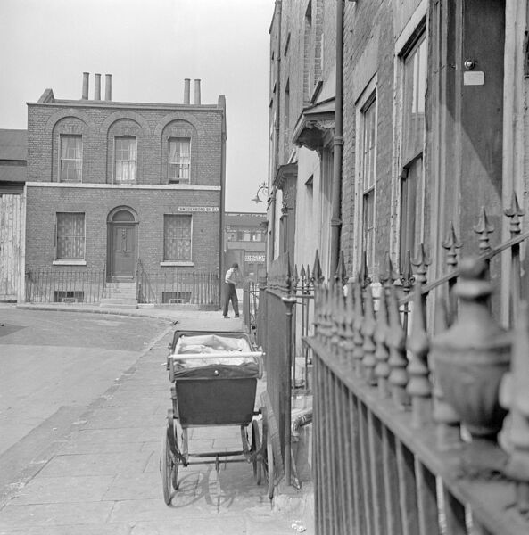 SWEDENBORG SQUARE, Stepney, London. A pram stands on the pavement outside a house in Swedenborg Square. A detached house stands on the corner. Photographed by Eric de Mare. Date range: 1945-1960