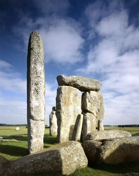STONEHENGE, Wiltshire. Detail of the sarsen trilithons showing tallest upright and station stone against a cloudy sky