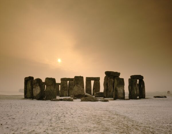 STONEHENGE, Wiltshire. Stones at sunset with snow in the foreground