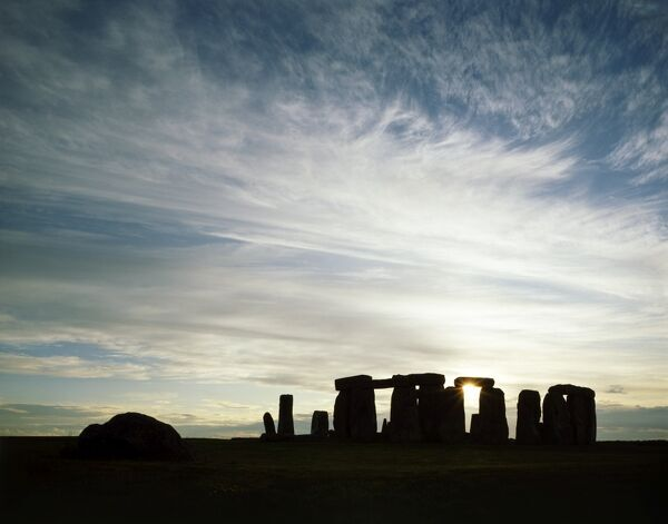 STONEHENGE, Wiltshire. Main circle and station stone silhouetted at sunset